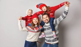 happy family mother, father and children in knitted hats and sweaters on gray background royalty free stock images