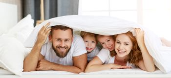 Happy family mother, father and children laughing, playing and smiling in bed   at home
