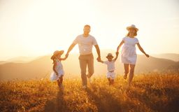 Happy family: mother, father, children son and daughter on sunset. Happy family: mother, father, children son and daughter on nature on sunset stock images
