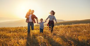 Happy family: mother, father, children son and daughter on sunse. Happy family: mother, father, children son and daughter on nature on sunset royalty free stock photos