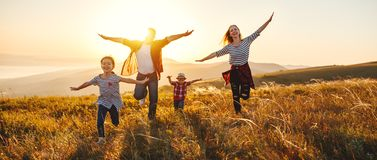 Happy family: mother, father, children son and daughter on sunset stock photos