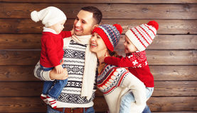 Happy family mother, father and children in winter hats on woode Stock Images