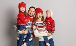 happy family mother, father and children in knitted hats and sweaters on gray background stock photo