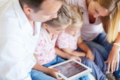 Happy family of mother, father and daughters sitting on a sofa a Stock Photos