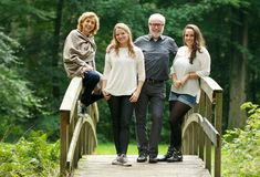 Happy family with mother father and daughters standing on bridge in the forest. Portrait of a happy family with mother father and daughters standing on bridge in Royalty Free Stock Image