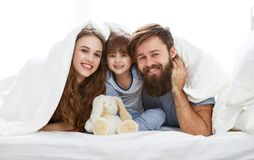 Happy family mother, father and child in bed royalty free stock image