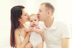 Happy family, mother and father kissing baby Royalty Free Stock Photography