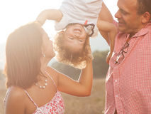 Happy family. Happy mother and father kissing their daughter in the park Stock Photo