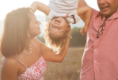 Happy family. Happy mother and father kissing their daughter in the park Stock Photography