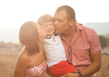 Happy family. Happy mother and father kissing their daughter in the park Royalty Free Stock Images