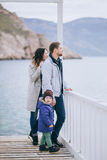 Happy family -mother, father and little son- walking in harbour. Near sea. Family wearing fashion clothes royalty free stock image
