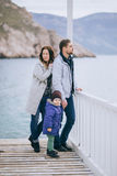 Happy family -mother, father and little son- walking in harbour. Near sea. Family wearing fashion clothes royalty free stock photography