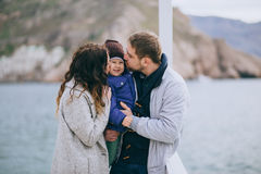 Happy family -mother, father and little son- walking in harbour. Near sea. Family wearing fashion clothes royalty free stock images