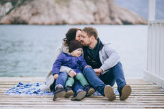 Happy family -mother, father and little son- walking in harbour. Near sea. Family wearing fashion clothes stock photo