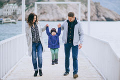 Happy family -mother, father and little son- walking in harbour. Near sea. Family wearing fashion clothes stock image