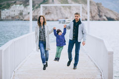 Happy family -mother, father and little son- walking in harbour. Near sea. Family wearing fashion clothes stock photography