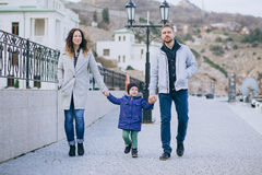 Happy family -mother, father and little son- walking in harbour Stock Photography