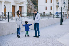 Happy family -mother, father and little son- walking in harbour. Happy family - mother, father and little son - wearing fashion clothes walking in a harbour on royalty free stock photo