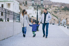 Happy family -mother, father and little son- walking in harbour. Happy family - mother, father and little son - wearing fashion clothes walking in a harbour on royalty free stock photography