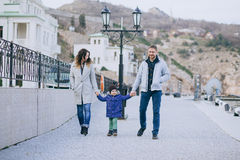 Happy family -mother, father and little son- walking in harbour. Happy family - mother, father and little son - wearing fashion clothes walking in a harbour on stock photos
