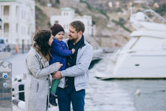 Happy family -mother, father and little son- walking in harbour. Happy family - mother, father and little son - wearing fashion clothes walking in a harbour on stock photography