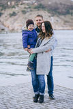 Happy family -mother, father and little son- walking in harbour. Happy family - mother, father and little son - wearing fashion clothes walking in a harbour on stock photo