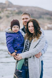 Happy family -mother, father and little son- walking in harbour. Happy family - mother, father and little son - wearing fashion clothes walking in a harbour on stock image