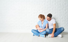 Happy family mother, father of a newborn baby on floor near blan Royalty Free Stock Image