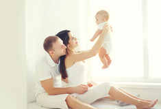 Happy family, mother and father playing with little baby home in white room near window Stock Photography