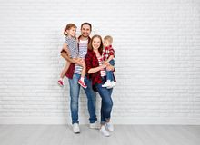 Happy family mother, father, son, daughter on a white blank wall. Happy family mother, father, son, daughter on a white blank brick wall background royalty free stock image