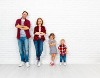 Happy family mother, father, son, daughter on a white blank wall. Happy family mother, father, son, daughter on a white blank brick wall background stock images