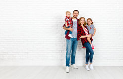 Happy family mother, father, son, daughter on a white blank wall. Happy family mother, father, son, daughter on a white blank brick wall background stock photos