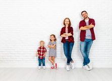 Happy family mother, father, son, daughter on a white blank wall. Happy family mother, father, son, daughter on a white blank brick wall background stock image