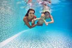 Happy family - mother, father, son dive underwater in swimming pool. Family fitness - mother, father, baby son learn to swim together, dive underwater with fun Royalty Free Stock Image