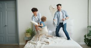 Happy family mother father son are fighting pillows at home on bed laughing. Enjoying game having fun together. Parents, children and apartments concept stock video footage