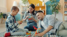 Happy family mother, father and son playing with construction toys at home talking