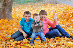 Happy family, mother, father and son sitting on the autumn leave Stock Images