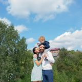 Happy family - mother, father and son on sky background in summer. Daddy mom and child son. Child sits on the shoulders royalty free stock photography