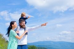 Happy family - mother, father and son on sky background in summer. Dream of flying. Happy family father and child on. Meadow with a kite in the summer on the stock photography