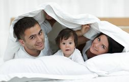 Happy family posing under a duvet while looking at the camera Stock Image