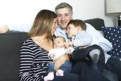 Happy family mother, father and two children at home Stock Images