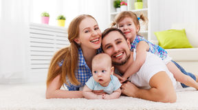 Happy family mother, father and two children playing and cuddling at home. On floor stock photos