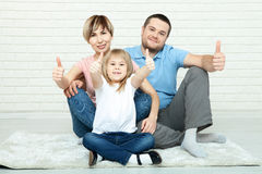Happy family mother, father and two children playing and cuddling at home on floor Royalty Free Stock Photo