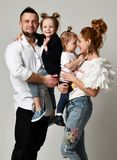 Happy family mother father and two daughter girls smiling on gray studio stock image