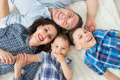 Happy family, mother, father and two sons having fun lying on the floor, upper view Stock Images