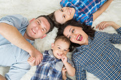 Happy family, mother, father and two sons having fun lying on the floor, upper view Royalty Free Stock Photography