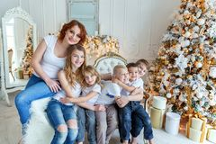 Mother and five children near Christmas tree at home stock photo