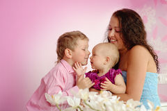 Happy family mother and her children boy and girl sitting indoor Stock Photography