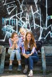 The happy family. Happy family - a mother and her daughters sit on the background of the wall with graffiti stock image