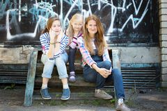 The happy family. Happy family - a mother and her daughters sit on the background of the wall with graffiti stock photos